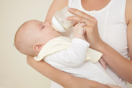 nourishing: Mother feeding newborn baby bottle of baby milk LANG_EVOIMAGES
