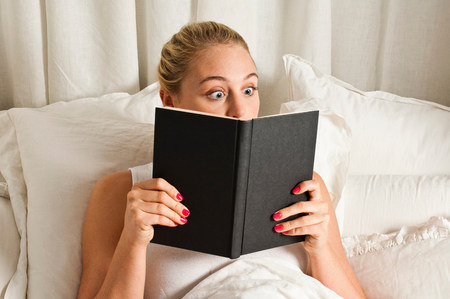 Surprised woman reading book in bed LANG_EVOIMAGES