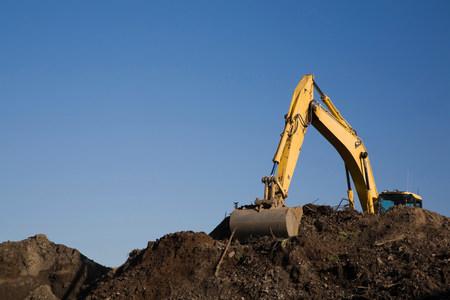 Excavator working on pile of topsoil