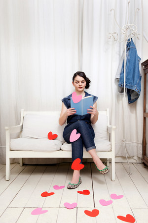 housing lot: Young woman reading book with heart shapes LANG_EVOIMAGES