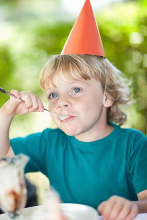 milestones: Boy having ice cream sundae at party LANG_EVOIMAGES