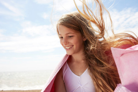 travel features: Girl by the sea wearing a towel,wind in her hair LANG_EVOIMAGES