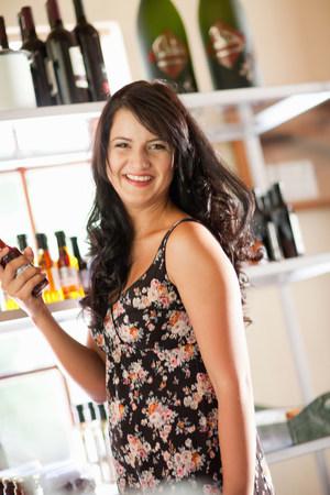 commodities: Mujer con botella de vinagre en la tienda de comestibles