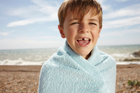 travel features: Boy at the beach,wrapped in a towel