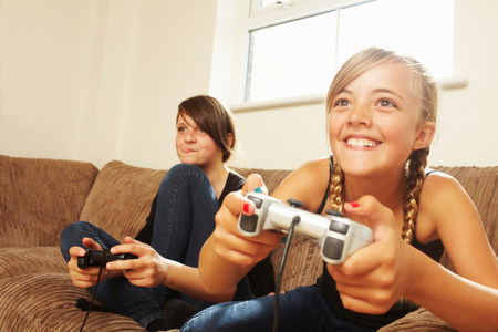 Two girls playing video game LANG_EVOIMAGES