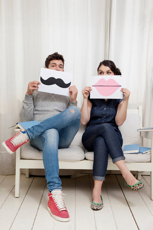 19 year old boy: Couple sitting on sofa holding lips and moustache