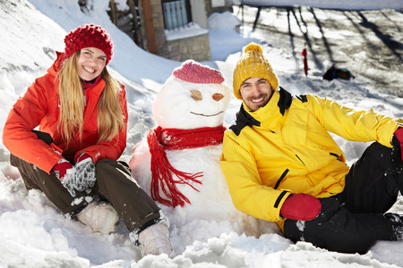 Couple sitting by snowman LANG_EVOIMAGES