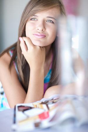 Teenage girl resting chin on hand