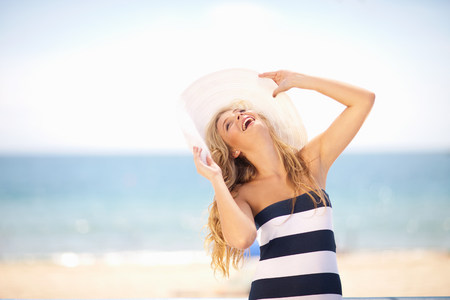 Woman wearing floppy hat on beach LANG_EVOIMAGES