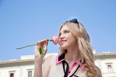 Young woman outdoors smelling rose