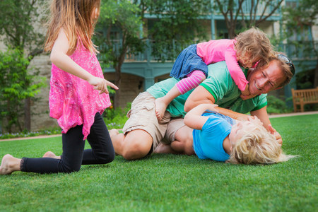 Father playing with his daughters in garden LANG_EVOIMAGES