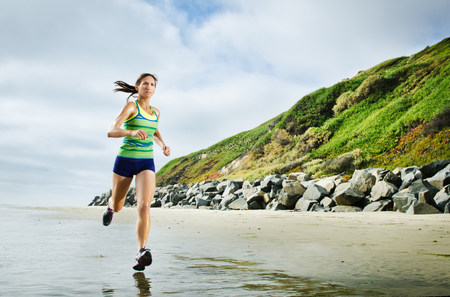 Woman running on beach LANG_EVOIMAGES