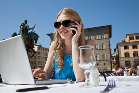 multi tasking: Young woman at restaurant outdoors,using laptop and cellphone