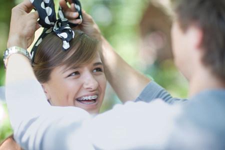 teenaged boy: Man tying headband on girlfriend