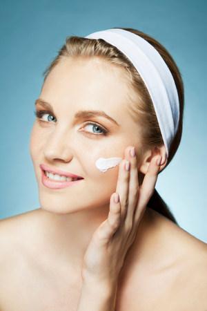 alice band: Woman applying moisturiser LANG_EVOIMAGES