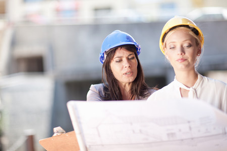 build in: Businesswomen reading blueprints