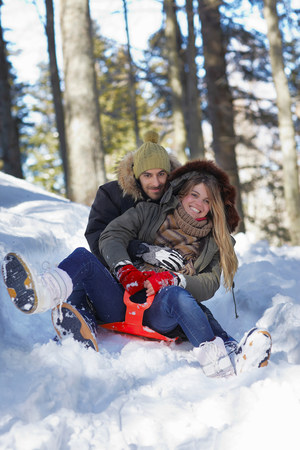 Couple tobogganing in snow