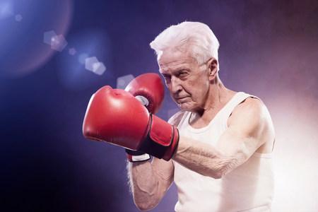 enraged: Senior man boxing