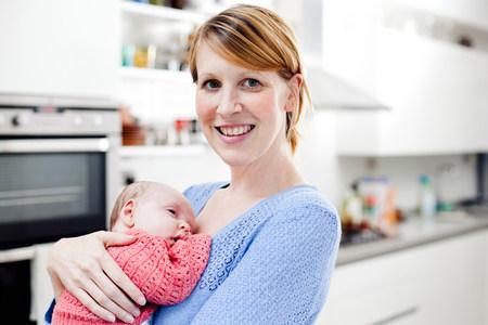Portrait of mother holding newborn daughter LANG_EVOIMAGES