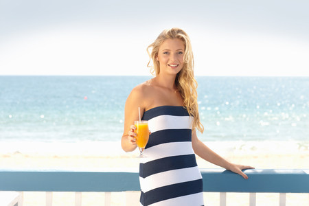 Woman drinking orange juice outdoors LANG_EVOIMAGES