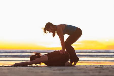 sunrises: Instructor helping woman into yoga pose on beach LANG_EVOIMAGES