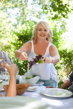 Woman serving salad at table outdoors