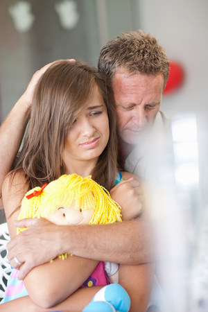 Father comforting teenage daughter LANG_EVOIMAGES