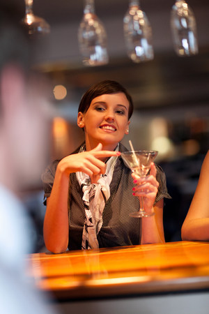 age 25 30 years: Woman ordering another drink at bar LANG_EVOIMAGES