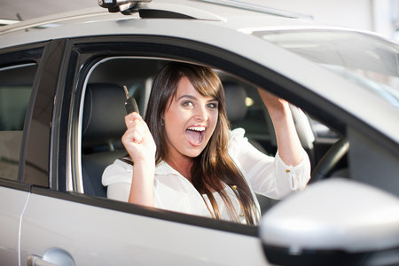 materialism: Cheering woman buying new car