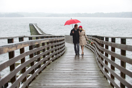 Couple walking on wooden pier in rain LANG_EVOIMAGES