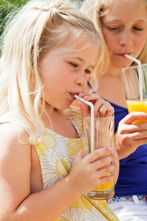 Two girls drinking orange juice