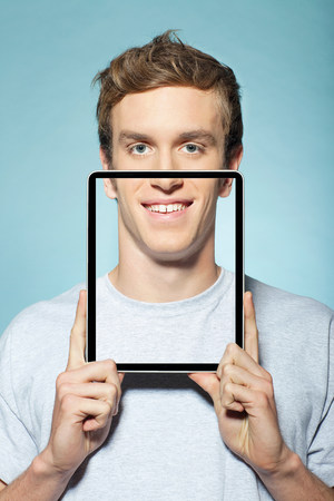 electronic organiser: Man covering half his face with digital tablet LANG_EVOIMAGES