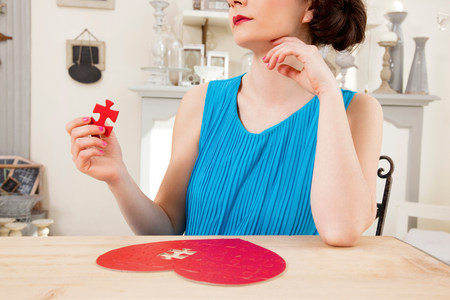 Woman doing heart shaped jigsaw puzzle holding piece LANG_EVOIMAGES