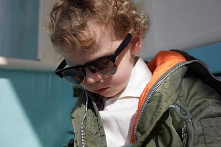Little boy wearing mod style sunglasses and parka