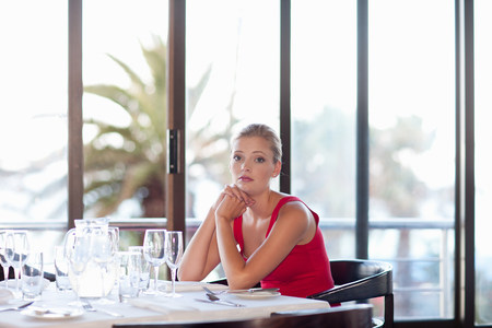 Woman sitting at restaurant table LANG_EVOIMAGES