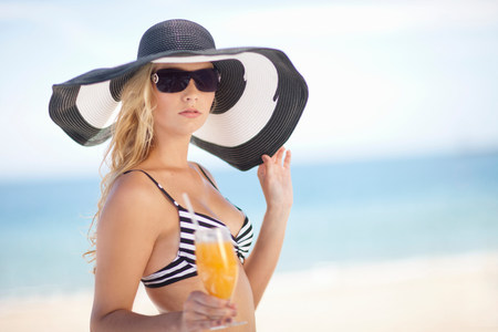 travel features: Woman in bikini and floppy hat on beach