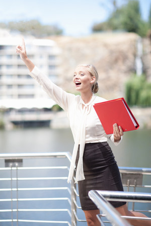 Businesswoman waving from balcony LANG_EVOIMAGES