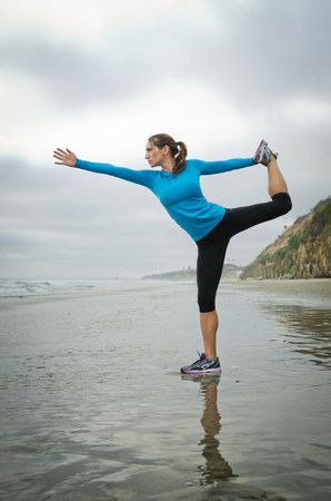 Runner practicing yoga on beach LANG_EVOIMAGES