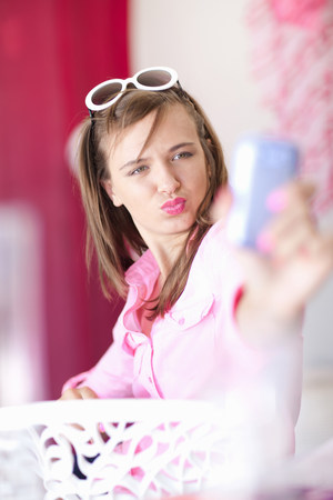 Teenage girl taking picture of herself LANG_EVOIMAGES