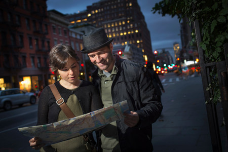 quizzical: Couple reading city map at night LANG_EVOIMAGES