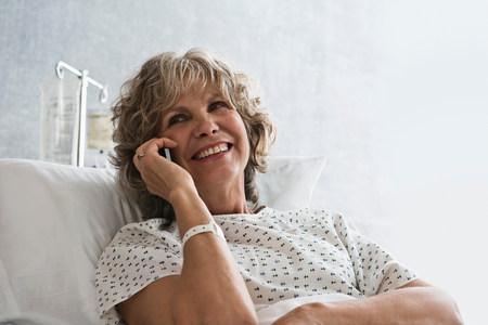 60 64 years: Female hospital patient using cellphone LANG_EVOIMAGES