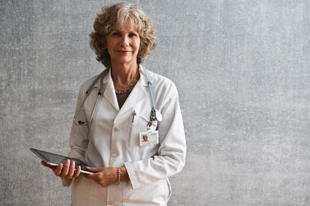 60 64 years: Female doctor holding digital tablet