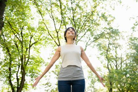 low self esteem: Smiling woman standing in park