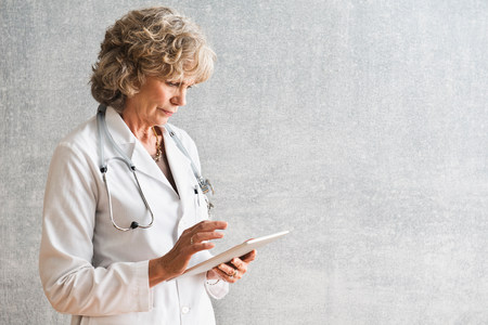 authoritative woman: Female doctor using at digital tablet LANG_EVOIMAGES