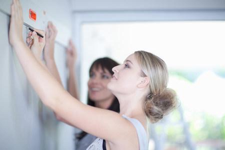 depth measurement: Woman working with interior designer LANG_EVOIMAGES