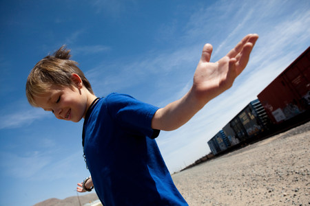 impulsive: Boy shrugging by train tracks