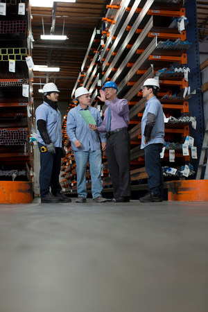 protects: Workers and businessman in metal plant LANG_EVOIMAGES