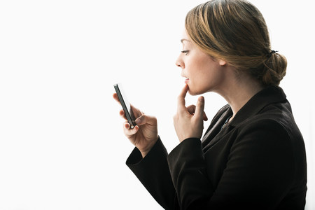 body parts cell phone: Businesswoman using smartphone as mirror