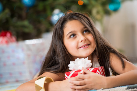 Girl holding Christmas present on floor LANG_EVOIMAGES