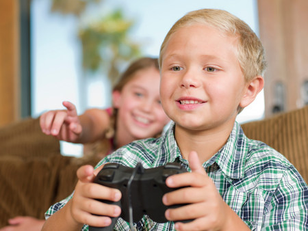 Children playing video games on sofa